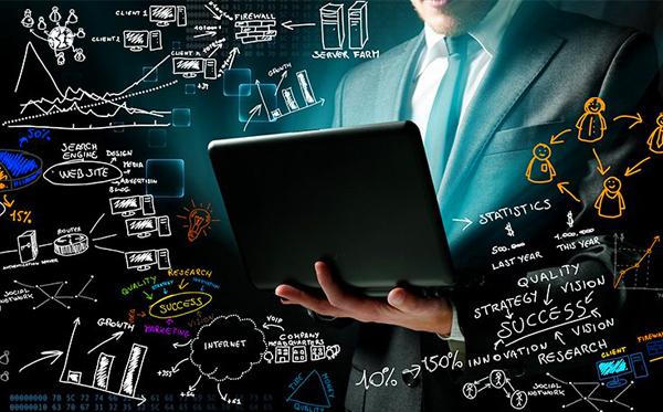 Смотрит в открытый ноутбук на черном фоне.